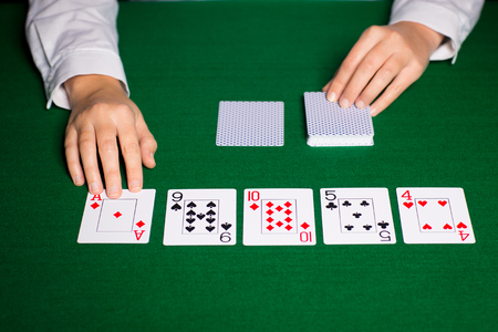 hold'em: casino, gambling, poker, people and entertainment concept - close up of holdem dealer hands with playing cards