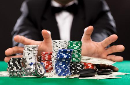 zábava: casino, hazardní hry, lidé a zábava koncepce - zavřít pokerový hráč s čipy, peníze a osobní věci na zelené kasino stůl