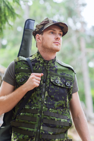 army men: hunting, war, army and people concept - young soldier, ranger or hunter with gun walking in forest