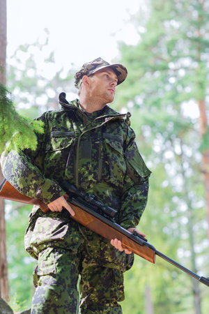 hunting rifle: hunting, war, army and people concept - young soldier, ranger or hunter with gun in forest Stock Photo