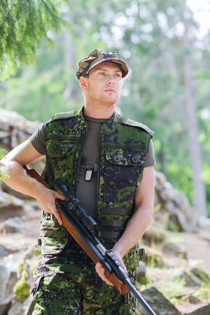 ranger: hunting, war, army and people concept - young soldier, ranger or hunter with gun in forest Stock Photo