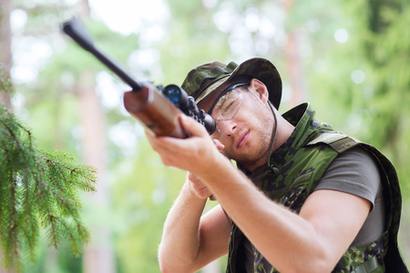 corps: hunting, war, army and people concept - young soldier, ranger or hunter with gun aiming and shooting in forest