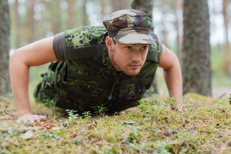 infantryman: war, army, training and people concept - young soldier or ranger wearing military uniform doing push-ups in forest