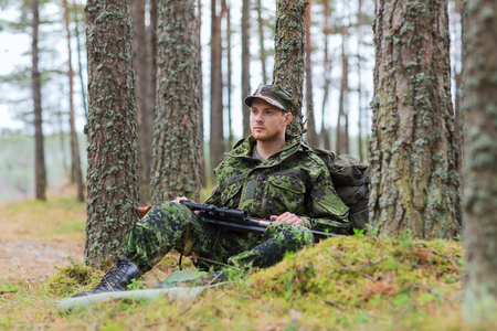 corps: hunting, war, army and people concept - young soldier, ranger or hunter with gun and backpack resting in forest