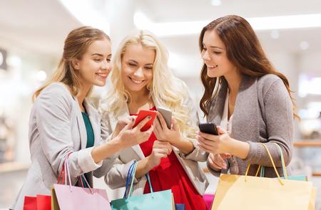 sprzedaż, konsumpcjonizm, technologii i koncepcji osób - szczęśliwe młode kobiety z torby na zakupy i smartfonów w centrum handlowym