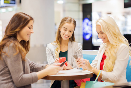 consumerism: sale, consumerism, technology and people concept - happy young women with smartphones and shopping bags in mall Stock Photo