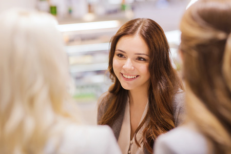talking people: communication, friendship and people concept - happy young women meeting and talking in mall or city