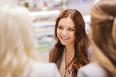 personas platicando: la comunicación, la amistad y el concepto de la gente - mujeres jóvenes felices conocer y hablar en el centro comercial o ciudad Foto de archivo