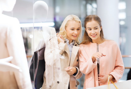 consumerism: sale, consumerism and people concept - happy young women with shopping bags pointing finger in mall