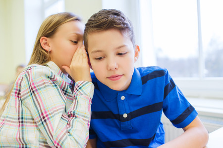 onderwijs, basisschool, leren en mensen concept - lachende schoolmeisje fluisteren geheim klasgenoot oor in de klas