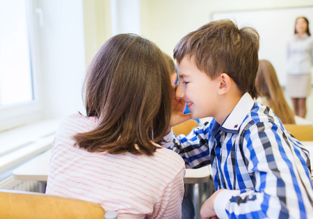 learners: education, elementary school, learning and people concept - smiling schoolgirl whispering secret to classmate ear in classroom Stock Photo