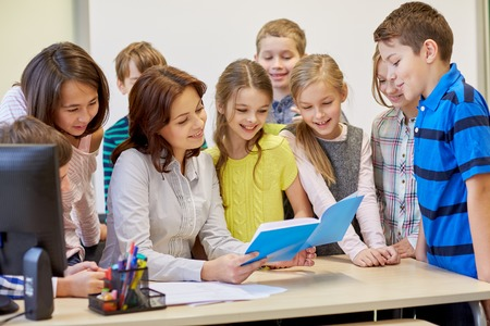 beautiful preteen girl: education, elementary school, learning and people concept - group of school kids with teacher talking in classroom