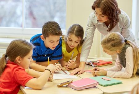 Onderwijs, basisschool, leren en mensen concept - leerkracht helpt schoolkinderen schriftelijk examen in de klas Stockfoto - 35024638