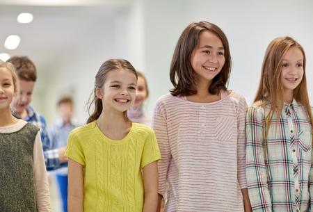 education, elementary school, drinks, children and people concept - group of smiling school kids walking in corridor