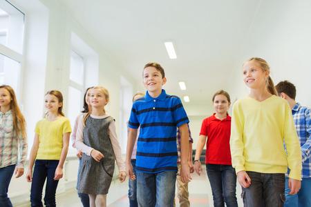 niños saliendo de la escuela: educación, escuela primaria, las bebidas, los niños y las personas concepto - grupo de niños de escuela sonriente caminando en el pasillo Foto de archivo