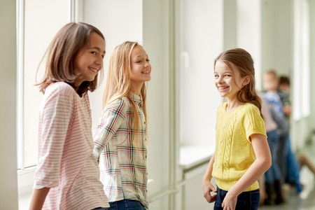 education, elementary school, children, break and people concept - group of smiling school kids in corridor