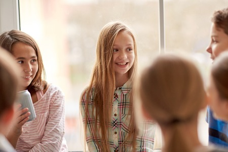 onderwijs, basisschool, drankjes, kinderen en mensen concept - groep schoolkinderen met blikjes frisdrank praten in de gang