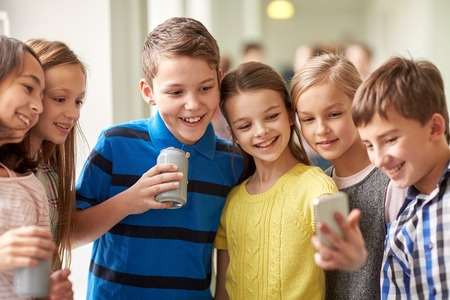 young girl smiling: education, elementary school, drinks, children and people concept - group of school kids with smartphone and soda cans taking selfie in corridor