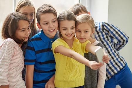 celulas humanas: educaci�n, escuela primaria, las bebidas, los ni�os y las personas concepto - grupo de ni�os de la escuela tomando Autofoto con el tel�fono inteligente en el pasillo
