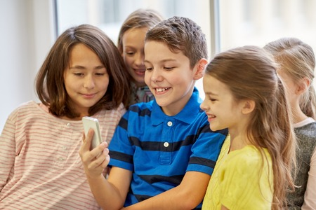 education, elementary school, drinks, children and people concept - group of school kids taking selfie with smartphone in corridor Stock Photo