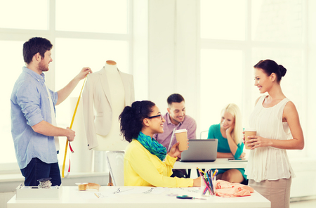 startup, education, fashion and office concept - smiling female designers having a coffee break in office with team on the back working photo