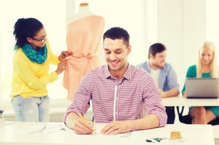 mannequin africain: démarrage, de l'éducation, de la mode et le concept de bureau - sourire croquis de dessin hommes et robe de réglage sur mannequin femelle dans le bureau