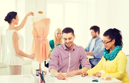 mannequin africain: démarrage, de l'éducation, de la mode et le concept de bureau - sourire concepteurs dessiner des croquis et en ajustant la robe sur mannequin dans le bureau Banque d'images