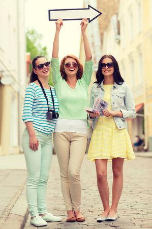 flechas direccion: turismo, viajes, vacaciones, dirección y concepto de amistad - sonrientes adolescentes con la flecha blanca que muestra la dirección al aire libre