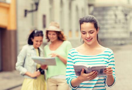 mujer leyendo libro: turismo, viajes, vacaciones y concepto de amistad - sonrientes adolescentes con guía de la ciudad, mapa y cámara en exteriores