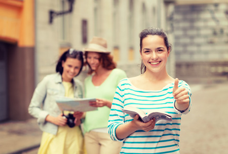 travel guide: tourism, travel, holidays and friendship concept - smiling teenage girls with city guide, map and camera showing thumbs up outdoors Stock Photo
