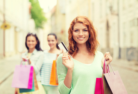 discount card: tourism, travel, vacation, shopping and friendship concept - smiling teenage girls with shopping bags on street