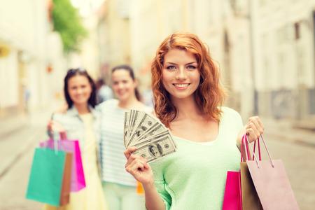 efectivo: turismo, viajes, vacaciones, ir de compras y el concepto de la amistad - sonrientes adolescentes con bolsas de compras en la calle Foto de archivo
