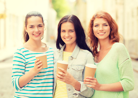 out in town: vacation, weekend, drinks and friendship concept - smiling teenage girls with coffee cups on street Stock Photo