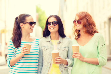 three girls: vacation, weekend, drinks and friendship concept - smiling teenage girls with coffee cups on street Stock Photo