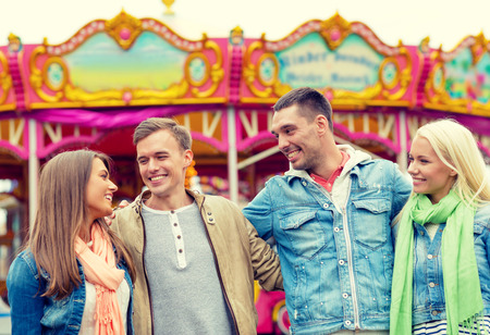 speak out: leisure, amusement park and friendship concept - group of smiling friends with carousel on the back Stock Photo