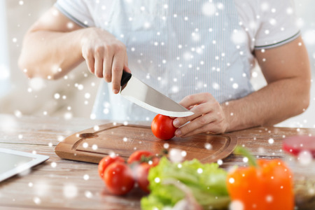 slicing: cooking, people, vegetarian food and home concept - close up of man chopping tomato and other vegetables on cutting board with big knife