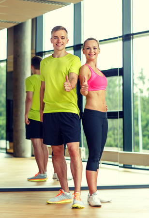 sport, fitness, lifestyle and people concept - smiling man and woman showing thumbs up in gym photo