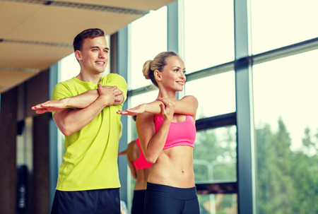 stretching: sport, fitness, lifestyle and people concept - smiling man and woman stretching in gym