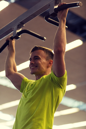 pullups: sport, fitness, lifestyle and people concept - smiling man doing pull-ups in gym