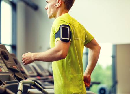 sport, fitness, lifestyle, technology and people concept - man with smartphone and earphones exercising on treadmill in gym Banque d'images