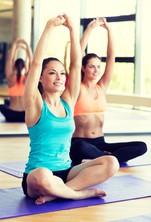 many hands: fitness, sport, training and lifestyle concept - group of smiling women stretching in gym