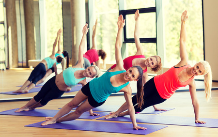 gyms: sport, meditation and lifestyle concept - smiling women meditating on mat in gym