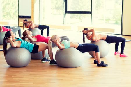 フィットネス、スポーツ、トレーニング、ライフ スタイル コンセプト - 笑顔の女性のグループ運動ジムでボール