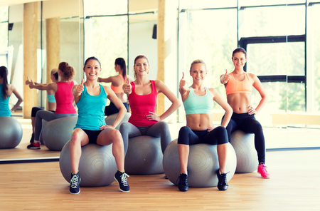 fitness, sport, training and gesture concept - group of smiling women showing thumbs up in gym photo