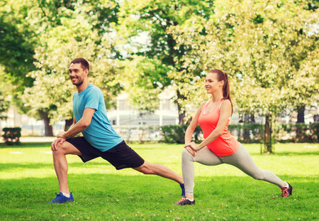 fitness, sport, training and lifestyle concept - smiling couple stretching outdoors photo