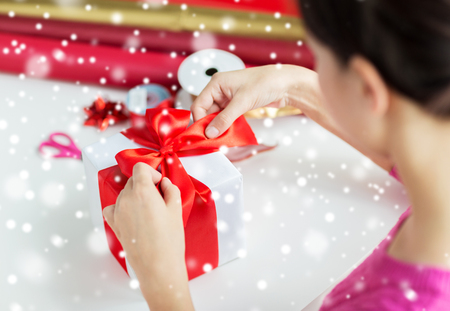 home decorating: holidays, people and celebration concept - close up of woman decorating christmas present at home