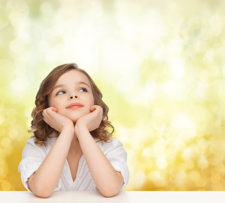 teenager thinking: children, childhood, holidays and happy people concept - beautiful girl sitting at table, looking up and dreaming over yellow lights background