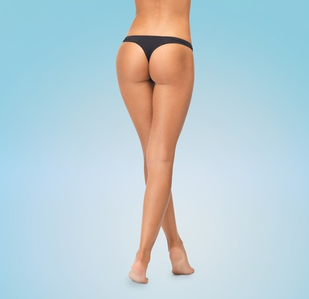 beauty, people and bodycare concept - close up of female legs in black bikini panties over blue background