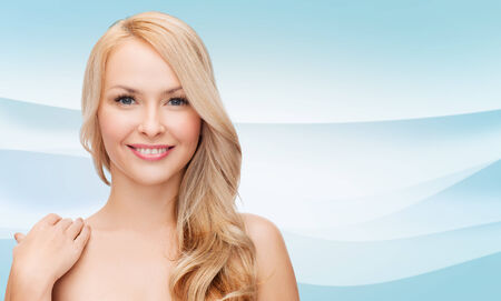 smooth hair: beauty, people and health concept - beautiful young woman with bare shoulders over blue waves background