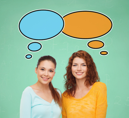 school, education, communication and people concept - smiling student girls over green board background with text bubbles photo
